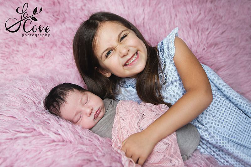 big sister photographed with newborn